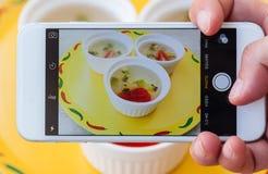 La foto della fragola della frutta ed il kiwi gelatinizzano il dessert tramite lo smartphone Fotografia Stock Libera da Diritti