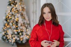 La foto della giovane donna sveglia con capelli scuri, vestita in maglione rosso tricottato, tiene lo Smart Phone in mani, ascolt fotografia stock