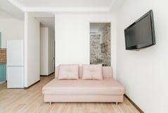 La foto della stanza luminosa con un sofà e la TV immagini stock libere da diritti