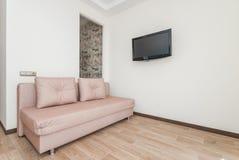 La foto della stanza luminosa con un sofà e la TV immagini stock