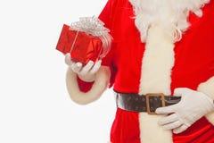 La foto delle mani gloved di Santa Claus che tengono il giftbox rosso, ha isolato fotografia stock