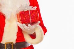 La foto delle mani gloved di Santa Claus che tengono il giftbox rosso, ha isolato immagine stock