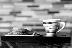 La foto di B&W della tazza e dei dolci di caffè è servito sulla tavola Immagine Stock
