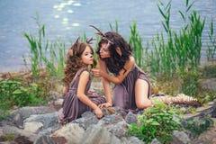 La foto di famiglia della madre e del bambino, fauno sulla riva di grande lago sta sedendo sulle pietre, caratteri di fiaba, immagini stock