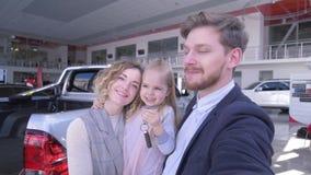 La foto di selfi della famiglia nel centro automatico, genitori con la ragazza sveglia del bambino con le chiavi prende la foto d