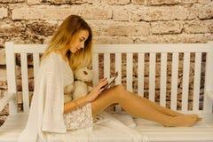 La foto horizontal de la chica joven que usa la tableta mientras que se sienta en el banco blanco Imagen de archivo libre de regalías