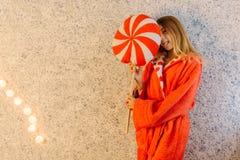 La foto horizontal del adolescente en el traje que oculta detrás del amortiguador de la piruleta y que muestra la lengua Imágenes de archivo libres de regalías