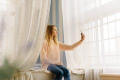La foto horizontal del adolescente que toma el selfie vía el teléfono mientras que se sienta en la cama Imagen de archivo libre de regalías