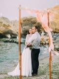 La foto integral de los recienes casados felices que miran la puesta del sol en el mar Imágenes de archivo libres de regalías