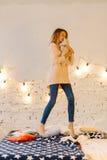 La foto integral preciosa de la muchacha rubia joven que abraza el oso de peluche y que salta en la cama Foto de archivo libre de regalías