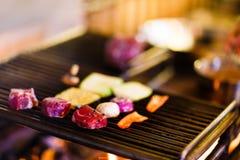 La foto lateral de la carne cruda condimentada y de las verduras frescas colocadas en el brasero en la cocina del restaurante Imagen de archivo