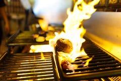 La foto lateral de la carne cruda que asa a la parrilla en el brasero con madera ardiente Imágenes de archivo libres de regalías