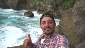 La foto masculina y la demostración del uno mismo que toma manosean con los dedos encima del paisaje hermoso cercano, olas oceáni almacen de video
