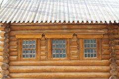La foto muestra la pared de una casa de madera con las ventanas fotos de archivo