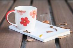 La foto oscura de la taza de café hermosa en el libro blanco en la tabla de madera con las hojas secadas con tono oscuro y la sel Imagen de archivo