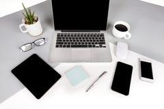 La foto plana de la endecha de la tabla de la oficina con el ordenador portátil, cuaderno, tableta digital, teléfono móvil en dos Fotografía de archivo libre de regalías