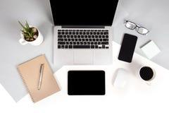 La foto plana de la endecha de la tabla de la oficina con el ordenador portátil, cuaderno, tableta digital, teléfono móvil en dos Foto de archivo libre de regalías