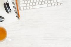La foto posta piana della scrivania con il trasduttore auricolare e la tastiera, copia lo spazio su fondo bianco con il taccuino  fotografia stock