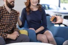 La foto potata di una coppia che è passata con l'automobile digita uno showro immagini stock libere da diritti