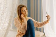 La foto preciosa del adolescente hermoso que toma el selfie vía el teléfono móvil en el dormitorio Imágenes de archivo libres de regalías