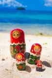 La foto rema la playa tropical sin tocar de las muñecas del rompecabezas de Matrioshka del recuerdo ruso de la familia en la isla Imagen de archivo libre de regalías