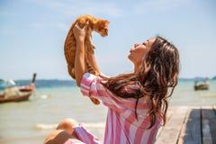 La foto sincera de la forma de vida atmosf?rica de la mujer asi?tica hermosa joven de vacaciones juega con un gato fotos de archivo