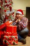 La foto vertical del inconformista triste con muchos regalos acerca a la Navidad Imagen de archivo libre de regalías