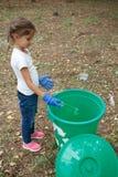 La foto verticale delle mani del ` s del bambino su variopinto ricicla nei guanti blu del lattice Fuori della foto, della terra e Fotografia Stock