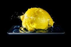 La foto volumétrica de un primer del limón adentro salpica del agua y de la luz del sol que caen en el agua en un smartphone aisl Imagenes de archivo