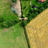 La fotografía aérea de las tierras de labrantío y de los prados cruzó por un pequeño arroyo domesticado, opinión aérea del extrac Fotografía de archivo