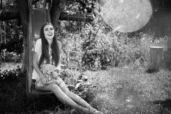 La fotografía blanca negra de la señora joven feliz se divierte en altozano del niño en patio al aire libre Fotos de archivo