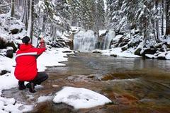 La fotografía en chaqueta roja con la cámara digital en manos está tomando la foto de la cascada del invierno Fotos de archivo libres de regalías