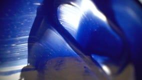 La fotografía macra como cuchillo de masilla mancha la pintura azul y blanca sobre el vidrio almacen de metraje de vídeo