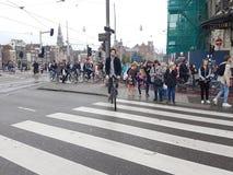La foule attend sur l'intersection de ville sur Damrak des lumières pour changer Photos stock