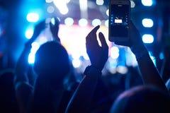 La foule de l'assistance avec des mains utilisant le téléphone d'appareil-photo pour prendre des photos et des vidéos au concert  images libres de droits
