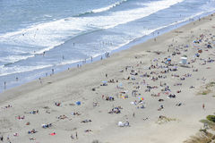 la foule de plage apprécie la vague déferlante images libres de droits