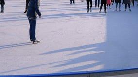 La foule des personnes patinent sur la patinoire dans Sunny Day banque de vidéos