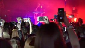 La foule faisant la partie au concert de rock et les mains tiennent beaucoup de caméras avec les affichages numériques parmi des  banque de vidéos