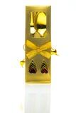 La fourchette et la cuillère en or enferment dans une boîte des couverts avec des ornements sur un fond blanc Photographie stock