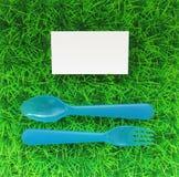 La fourchette et la cuillère en plastique sur une pelouse verte avec une carte de visite professionnelle de visite complètent Image stock