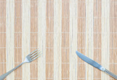 La fourchette et le couteau inoxydables de plan rapproché sur le tapis en bois ont donné au fond une consistance rugueuse avec l' Photographie stock