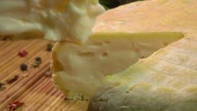 La fourchette et le couteau soul?ve un morceau de fromage de moutons banque de vidéos