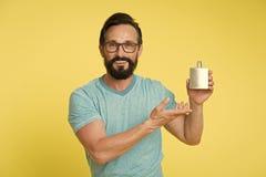 La fragancia correcta del perfume le hace más joven Perfume sonriente hermoso barbudo de la botella del control de la cara del ho fotografía de archivo libre de regalías