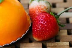 La fragola del primo piano per decora sul dolce arancio sulla stuoia di legno Fotografia Stock