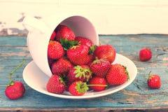 La fragola di giardino è sparsa dalla tazza in un piattino Fotografia Stock Libera da Diritti