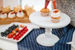La fraise a rempli petits gâteaux de givrage crémeux sur le plateau blanc de portion, foyer sélectif photo libre de droits