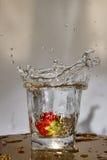 La fraise tombe avec une éclaboussure dans l'eau Images libres de droits