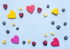 La frambuesa y el mango del arándano, los corazones decorativos alinearon el marco en el fondo azul, espacio para el texto Fotos de archivo