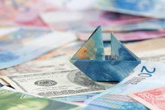 La France suisse pliée comme bateau sur des devises du monde Photo stock