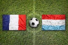 La Francia contro Bandiere del Lussemburgo sul campo di calcio Fotografia Stock